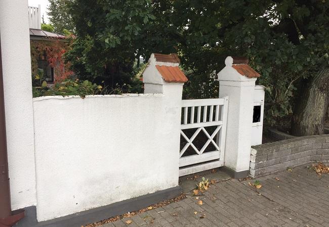 mur med grindstolpar och grind
